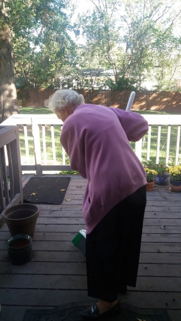 mom-sweeping-acorns-on-back-deck-oct-2016